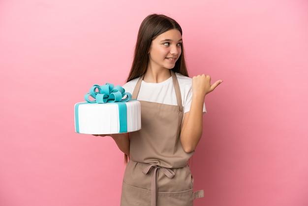 Bambina con una grande torta su sfondo rosa isolato che punta al lato per presentare un prodotto