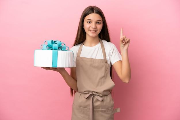 Bambina con una grande torta su sfondo rosa isolato che indica una grande idea