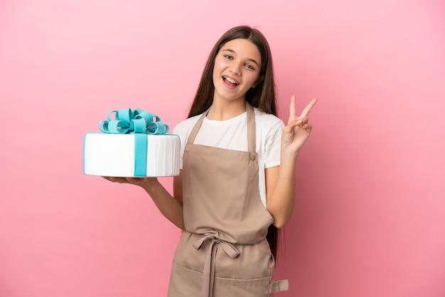 Bambina con una grande torta su sfondo rosa isolato che sorride e mostra il segno della vittoria