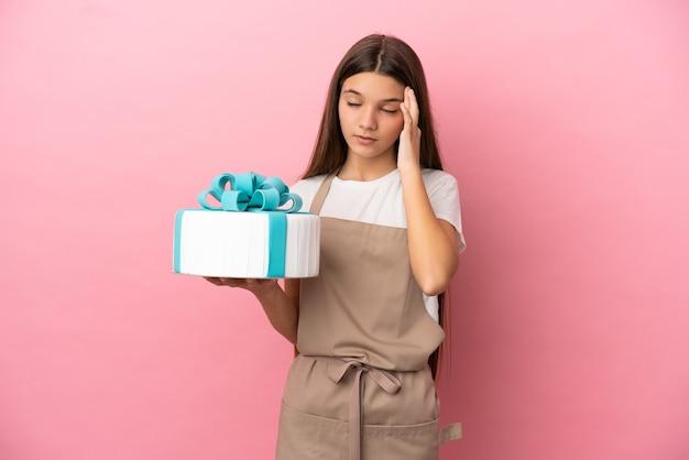 Bambina con una grande torta sulla superficie rosa isolata con mal di testa
