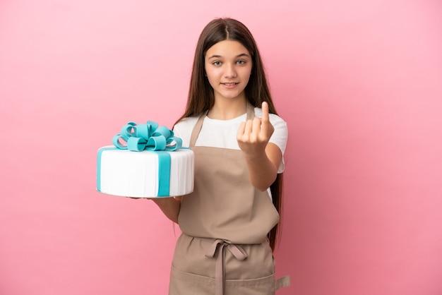 Bambina con una grande torta sul muro rosa isolato che fa un gesto imminente
