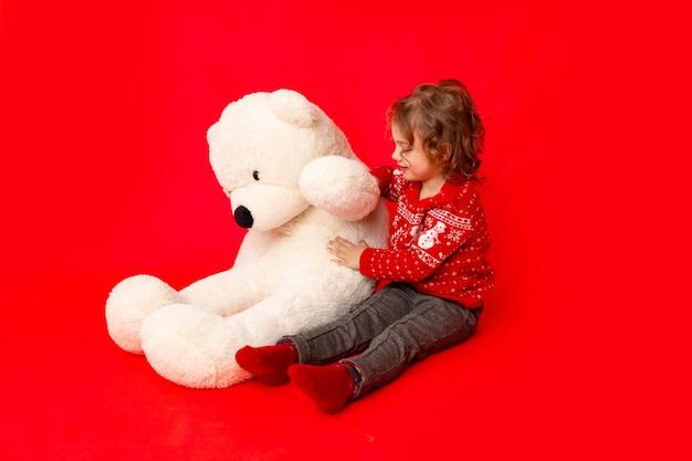 Bambina con un grande orsacchiotto in abiti invernali su uno sfondo rosso, spazio per il testo