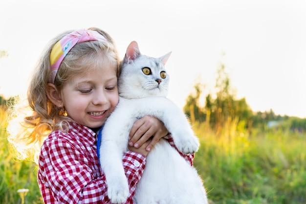 Una bambina con un grosso gatto scozzese bianco tra le braccia ama gli animali