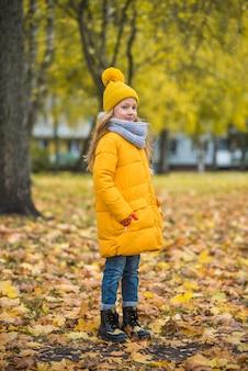Bambina con capelli biondi nella sosta di autunno