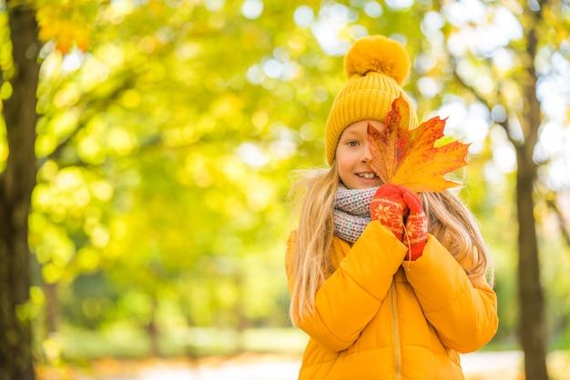 Bambina con capelli biondi in autunno in abiti gialli