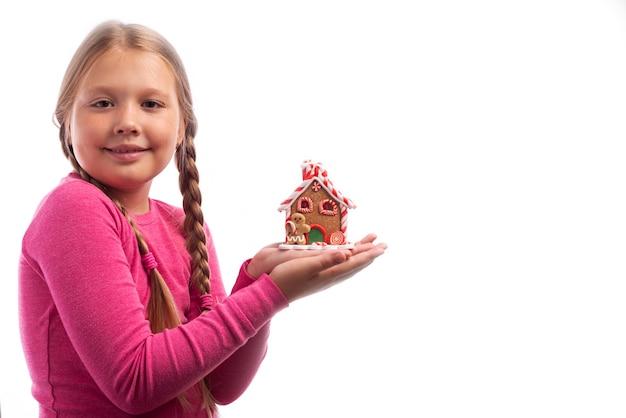 Bambina con capelli biondi che tiene una casa di pan di zenzero nelle sue mani su un fondo bianco