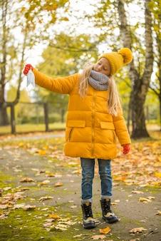 Bambina con capelli biondi che tiene mascherina medica nella sosta di autunno