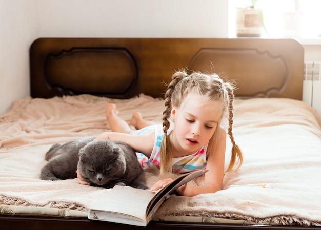 Una bambina dai capelli biondi giace su un letto a casa con un gatto che legge un libro. resta a casa. istruzione a casa per i bambini.