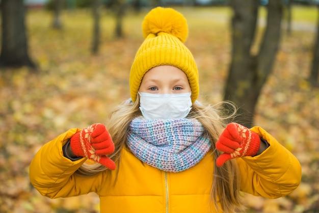 Bambina con capelli biondi che indossa la mascherina medica nel parco d'autunno