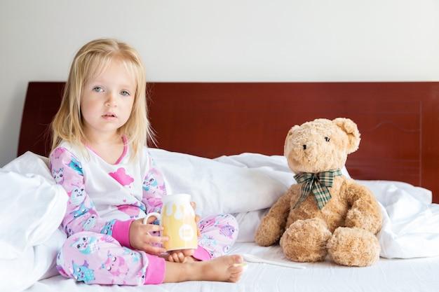 Bambina con capelli biondi che si siede sul letto con l'orsacchiotto farcito