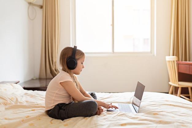Bambina con capelli biondi che resta a casa e che per mezzo del computer portatile