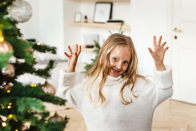 Bambina con capelli biondi in un maglione bianco giocando vicino all'albero di natale, ridendo, sorridente,