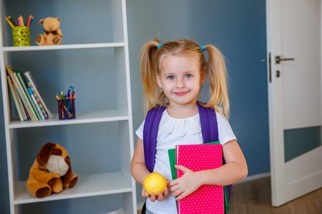 Una bambina con un libro e una mela tra le mani