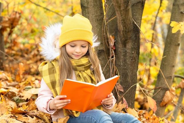 Una bambina con un libro sulle foglie d'autunno.