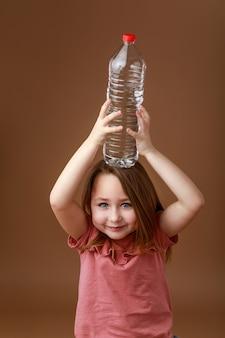 Bambina con una bottiglia d'acqua in testa