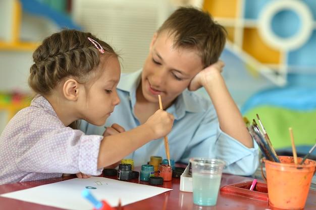 Bambina con bambino che disegna a casa