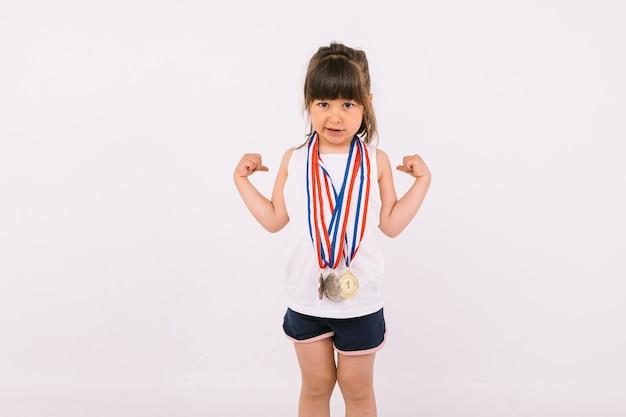 Bambina con i capelli castani con medaglie di campioni sportivi sul collo che fanno il simbolo della forza. sport e concetto di vittoria