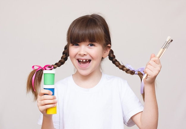 Bambina con un pennello e vernici
