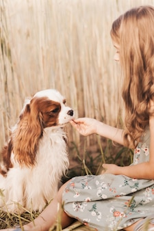 Bambina con un cane cavalier king charles spaniel che gioca in estate nella natura