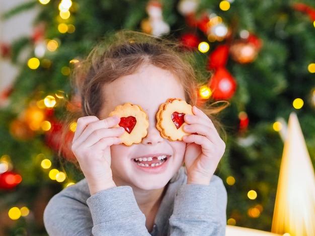 Bambina con cambio di denti che producono i biscotti di natale e gioco sotto l'albero di natale nella sala con le luci di natale