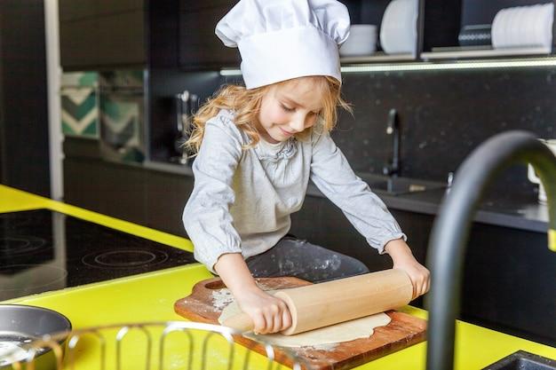 Bambina con cappello da chef, mattarello che prepara l'impasto, cuocere la torta di mele fatta in casa per le vacanze in cucina. bambino che cucina cibo sano a casa e si diverte. infanzia, famiglia, concetto di aiuto del lavoro di squadra