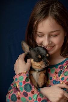 Bambina con un chihuahua. chihuahua della holding della ragazza. ragazza con il suo animale domestico tra le braccia. chihuahua in colore bianco marrone nero. i bambini amano i loro animali. ragazza e chihuahua. i bambini amano i loro animali