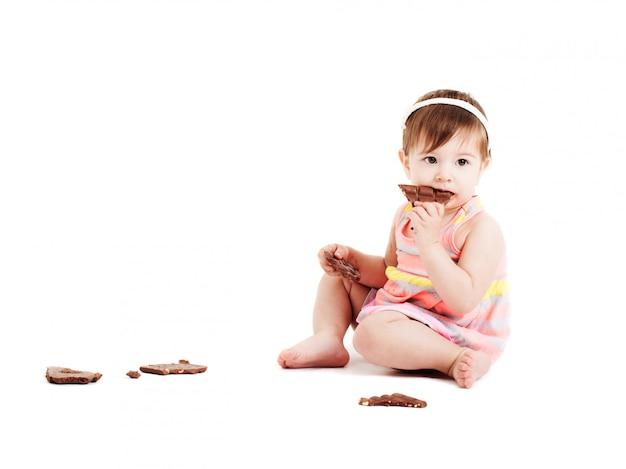 Bambina con cioccolato isolato su bianco