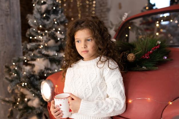 Bambina con la tazza di natale del tee vicino all'automobile rossa e agli alberi di natale con le luci. buon natale e buone feste