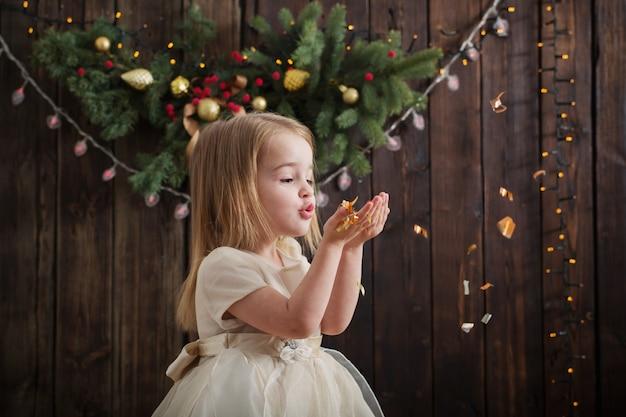 Bambina con le decorazioni di natale su legno scuro