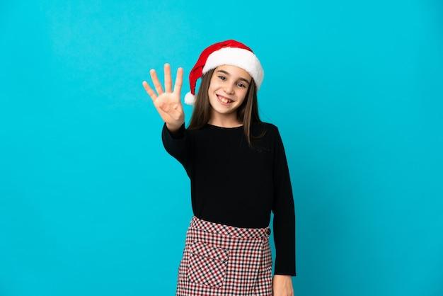 Bambina con cappello di natale isolato su sfondo blu felice e contando quattro con le dita