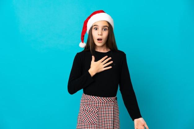 Bambina con il cappello di natale isolato sulla parete blu sorpresa e scioccata mentre guarda a destra