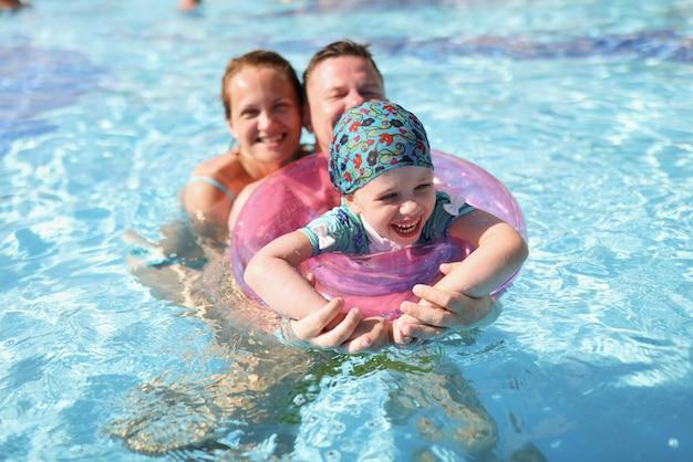 Bambina con cerchio e genitori che nuotano in piscina