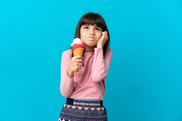 Bambina con un gelato alla cornetta isolato su sfondo blu frustrato e che copre le orecchie
