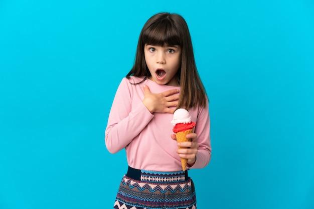 Bambina con un gelato alla cornetta isolato su sfondo blu sorpreso e scioccato mentre guardava a destra