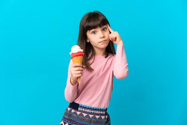 Bambina con un gelato alla cornetta isolato su sfondo blu pensando a un'idea