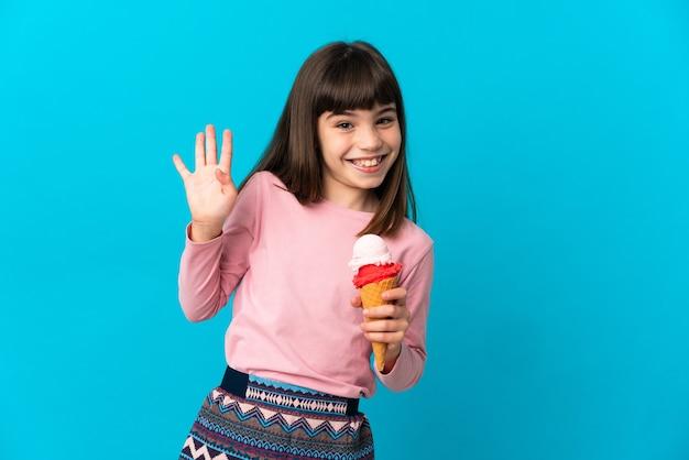 Bambina con un gelato alla cornetta isolato sulla parete blu che saluta con la mano con l'espressione felice