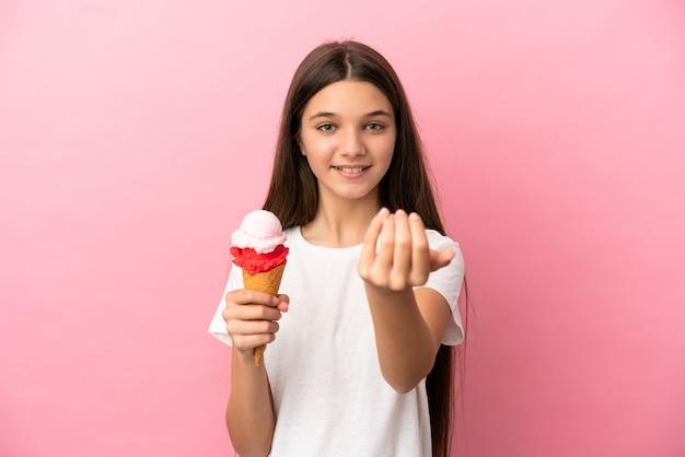 Bambina con un gelato alla cornetta su sfondo rosa isolato che invita a venire con la mano. felice che tu sia venuto