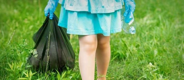Bambina con la bottiglia di plastica sgualcita e il sacco della spazzatura nelle sue mani durante la pulizia dei rifiuti nel parco