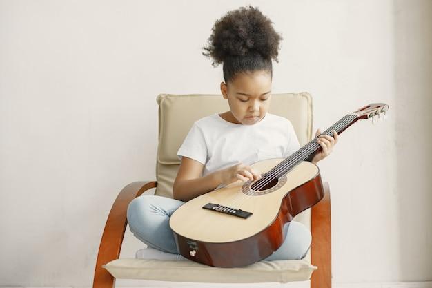 Bambina con i capelli ricci. imparare a suonare la chitarra. bambina su una sedia.