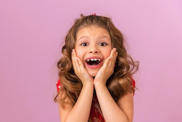 Una bambina con i capelli ricci e un vestito rosso è molto sorpresa sullo sfondo rosa