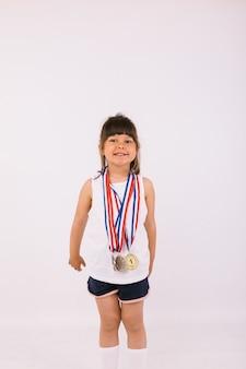 Bambina con i capelli scuri con medaglie di campione sportivo. sport e concetto di vittoria
