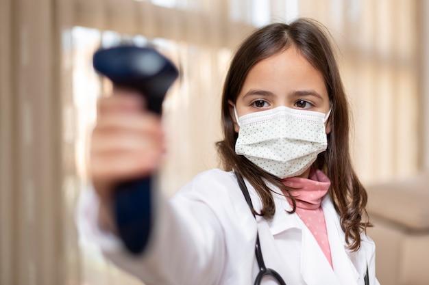 Bambina con l'uniforme del medico e mascherina medica utilizzando un termometro a infrarossi