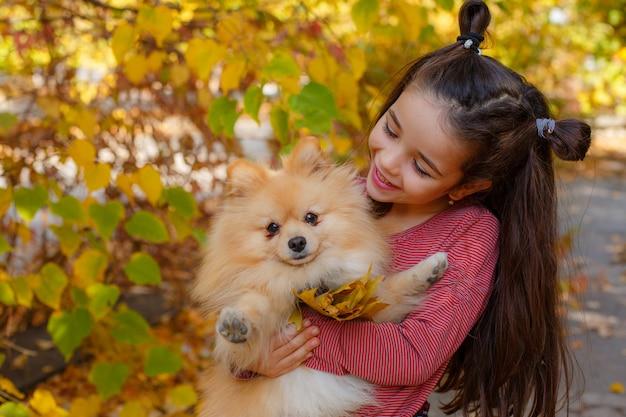 Bambina con un cane in autunno nel parco per una passeggiata