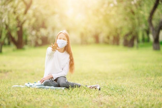 La bambina con il cane che indossa la maschera medica protettiva per impedisce il virus all'aperto nel parco