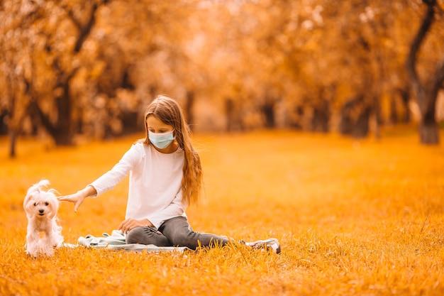 Bambina con cane che indossa maschera medica protettiva per prevenire virus all'aperto nel parco