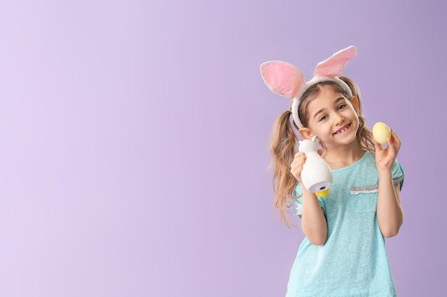 Bambina con l'uovo di pasqua e il coniglietto sopra la parete viola con lo spazio della copia