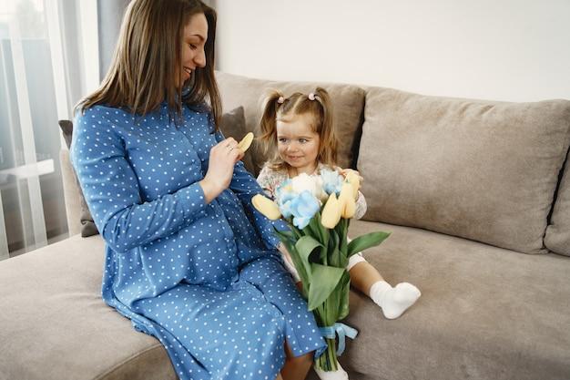 Bambina con fiori. la mamma è incinta. saluti per la mamma.