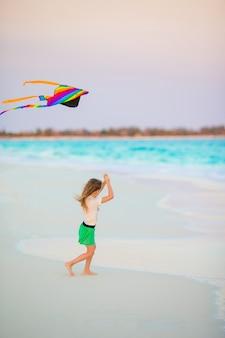 Bambina con l'aquilone di volo sulla spiaggia tropicale. gioco per bambini sulla riva dell'oceano. bambino con giocattoli da spiaggia.