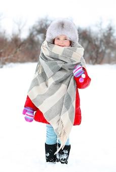 Bambina con cappello di pelliccia e stola nel parco invernale all'aperto