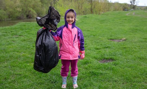 Una bambina con un sacco della spazzatura in viaggio nella natura per pulire l'ambiente.